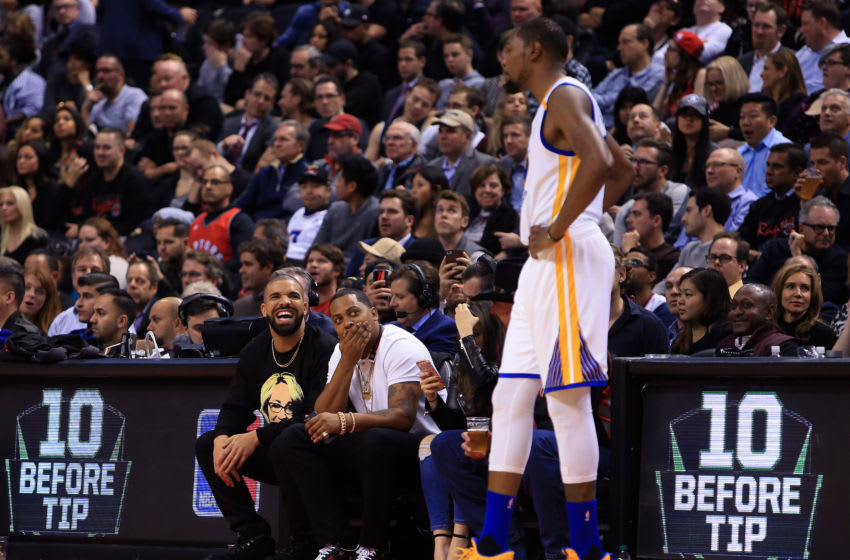 TORONTO, ON - NOVEMBER 16: Drake laughs with Kevin Durant #35 of the Golden State Warriors in the second half of an NBA game against the Toronto Raptors at Air Canada Centre on November 16, 2016 in Toronto, Canada. NOTE TO USER: User expressly acknowledges and agrees that, by downloading and or using this photograph, User is consenting to the terms and conditions of the Getty Images License Agreement. (Photo by Vaughn Ridley/Getty Images)
