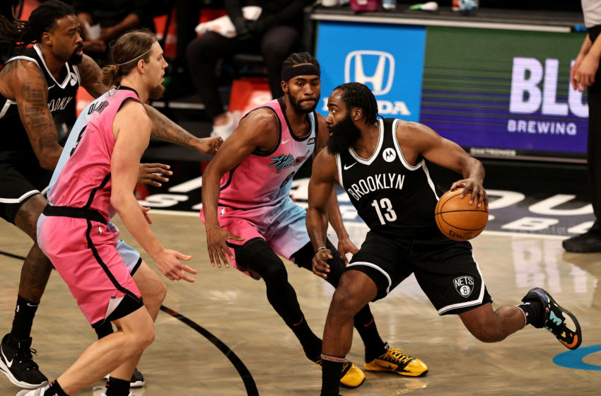 NEW YORK, NEW YORK - JANUARY 23: James Harden #13 of the Brooklyn Nets drives around Kelly Olynyk #9 and Maurice Harkless #8 of the Miami Heat (Photo by Elsa/Getty Images)