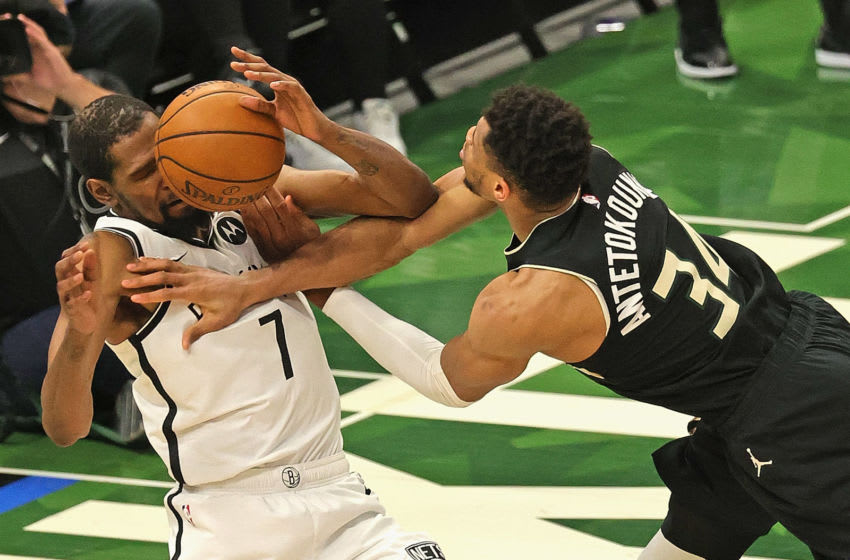MILWAUKEE, WISCONSIN - JUNE 17: Giannis Antetokounmpo #34 of the Milwaukee Bucks looses control of the ball after being fouled by Kevin Durant #7 of the Brooklyn Nets at Fiserv Forum on June 17, 2021 in Milwaukee, Wisconsin. The Bucks defeated the Nets 104-89. NOTE TO USER: User expressly acknowledges and agrees that, by downloading and or using this photograph, User is consenting to the terms and conditions of the Getty Images License Agreement. (Photo by Jonathan Daniel/Getty Images)