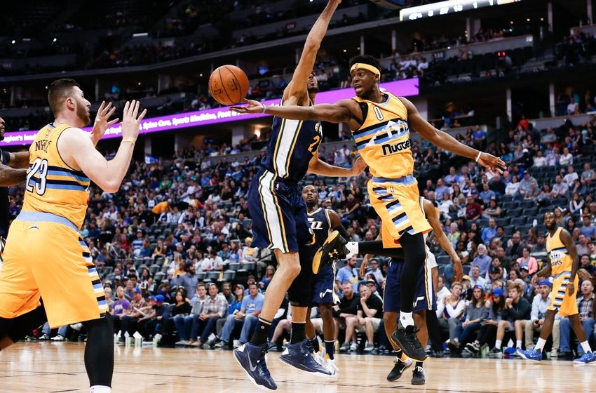 Apr 10, 2016; Denver, CO, USA; Denver Nuggets guard Emmanuel Mudiay (0) passes the ball to center Jusuf Nurkic (23) around Utah Jazz center Rudy Gobert (27) in the third quarter at the Pepsi Center. The Jazz defeated the Nuggets 100-84. Mandatory Credit: Isaiah J. Downing-USA TODAY Sports
