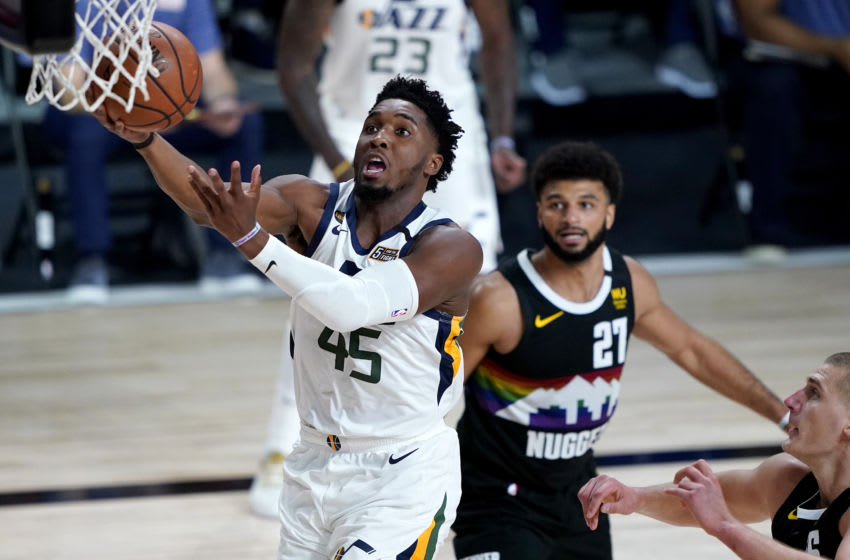 LAKE BUENA VISTA, FLORIDA - AUGUST 19: Donovan Mitchell #45 of the Utah Jazz drives to the basket as Jamal Murray #27 of the Denver Nuggets look on during the first half of Game Two of a first round playoff game at AdventHealth Arena at ESPN Wide World Of Sports Complex on August 19, 2020 in Lake Buena Vista, Florida. NOTE TO USER: User expressly acknowledges and agrees that, by downloading and or using this photograph, User is consenting to the terms and conditions of the Getty Images License Agreement. (Photo by Ashley Landis-Pool/Getty Images)