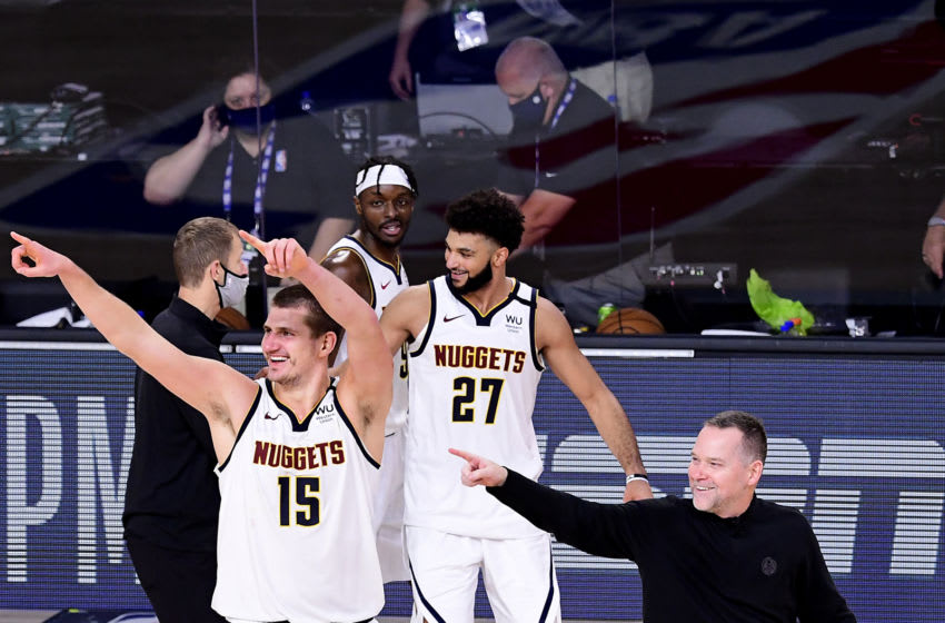 LAKE BUENA VISTA, FLORIDA - SEPTEMBER 15: Michael Malone of the Denver Nuggets, Nikola Jokic #15 of the Denver Nuggets and Jamal Murray #27 of the Denver Nuggets celebrate their win over LA Clippers in Game Seven of the Western Conference Second Round during the 2020 NBA Playoffs at AdventHealth Arena at the ESPN Wide World Of Sports Complex on September 15, 2020 in Lake Buena Vista, Florida. NOTE TO USER: User expressly acknowledges and agrees that, by downloading and or using this photograph, User is consenting to the terms and conditions of the Getty Images License Agreement. (Photo by Douglas P. DeFelice/Getty Images)