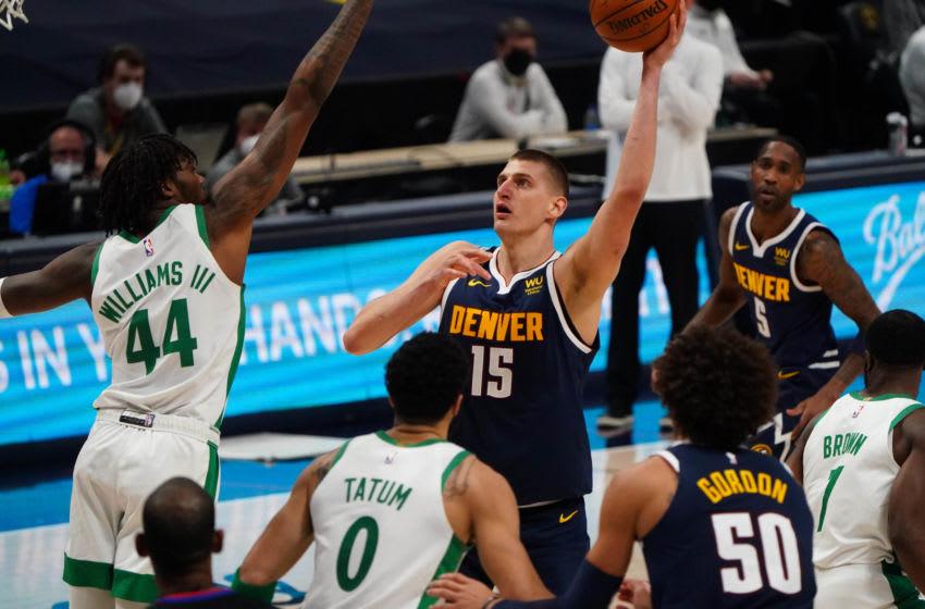 Apr 11, 2021; Denver, Colorado, USA; Denver Nuggets center Nikola Jokic (15) lines up a shot over Boston Celtics center Robert Williams III (44) in the third quarter at Ball Arena. Mandatory Credit: Ron Chenoy-USA TODAY Sports