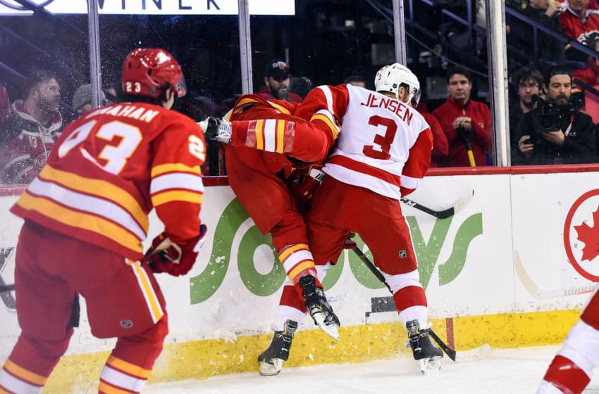 CALGARY, AB - JANUARY 18: Detroit Red Wings Defenceman Nick Jensen (3) checks Calgary Flames Defenceman T.J. Brodie (7) into the board during the second period of an NHL game where the Calgary Flames hosted the Detroit Red Wings on January 18, 2019, at the Scotiabank Saddledome in Calgary, AB. (Photo by Brett Holmes/Icon Sportswire via Getty Images)