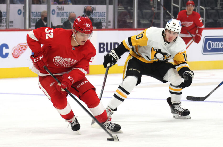 DETROIT, MICHIGAN - OCTOBER 07: Jonatan Berggren #52 of the Detroit Red Wings tries to control the puck in front of Drew O'Connor #10 of the Pittsburgh Penguins during the first period in a pre season game at Little Caesars Arena on October 07, 2021 in Detroit, Michigan. (Photo by Gregory Shamus/Getty Images)