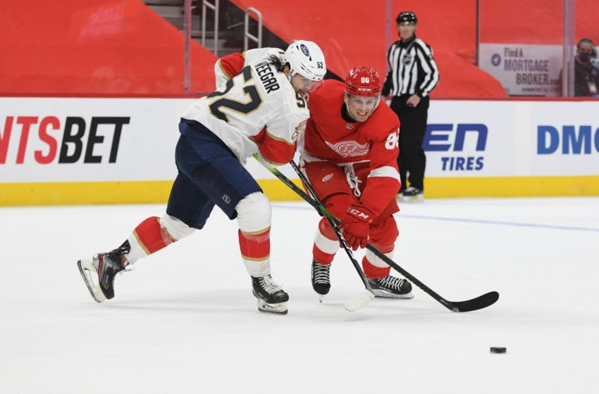 Jan 30, 2021; Detroit, Michigan, USA; Florida Panthers defenseman MacKenzie Weegar (52) and Detroit Red Wings left wing Mathias Brome (86) battle for the puck during overtime at Little Caesars Arena. Mandatory Credit: Tim Fuller-USA TODAY Sports