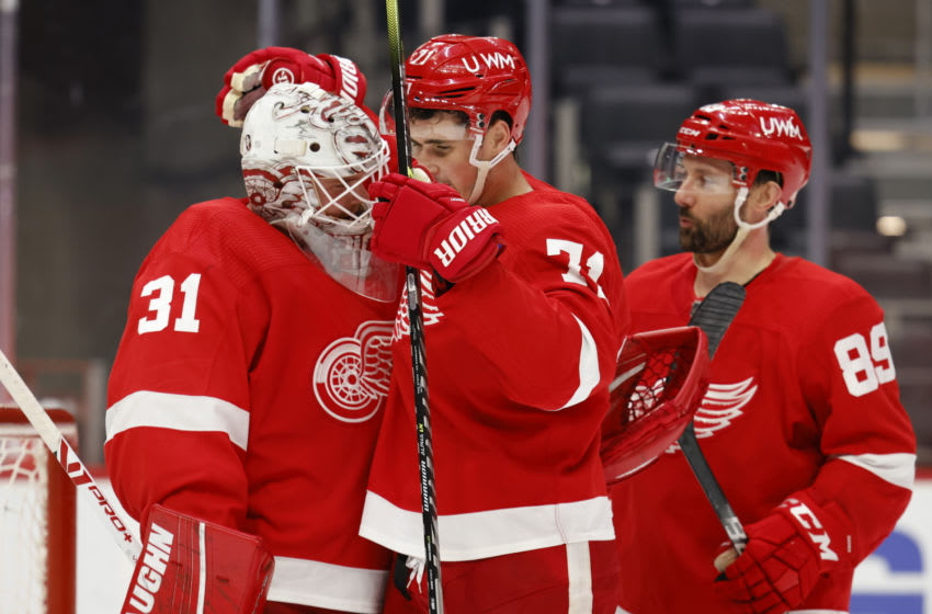 Mar 28, 2021; Detroit, Michigan, USA; Detroit Red Wings goaltender Calvin Pickard (31) receives congratulations from center Dylan Larkin (71) and center Sam Gagner (89) after the game against the Columbus Blue Jackets at Little Caesars Arena. Mandatory Credit: Rick Osentoski-USA TODAY Sports