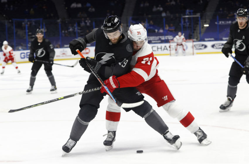 Apr 3, 2021; Tampa, Florida, USA; Tampa Bay Lightning right wing Barclay Goodrow (19) and Detroit Red Wings center Dylan Larkin (71) fight to control the puck during the second period at Amalie Arena. Mandatory Credit: Kim Klement-USA TODAY Sports