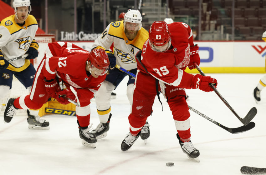 Apr 8, 2021; Detroit, Michigan, USA; Detroit Red Wings defenseman Brian Lashoff (32) Nashville Predators defenseman Mattias Ekholm (14) and center Sam Gagner (89) battle for the puck in the second period at Little Caesars Arena. Mandatory Credit: Rick Osentoski-USA TODAY Sports