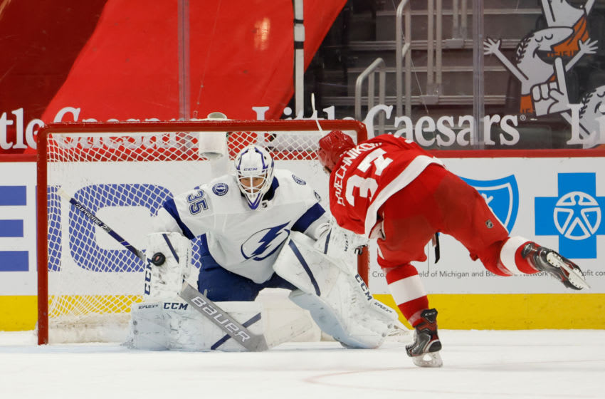 May 1, 2021; Detroit, Michigan, USA; Tampa Bay Lightning goaltender Curtis McElhinney (35) makes the save on Detroit Red Wings left wing Evgeny Svechnikov (37) during a shootout at Little Caesars Arena. Mandatory Credit: Rick Osentoski-USA TODAY Sports