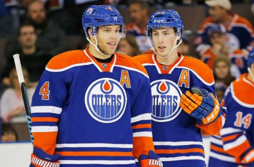 Nov 20, 2015; Edmonton, Alberta, CAN; Edmonton Oilers forward Taylor Hall (4) and forward Ryan Nugent-Hopkins (93) talk between whistles against the New Jersey Devils at Rexall Place. Mandatory Credit: Perry Nelson-USA TODAY Sports