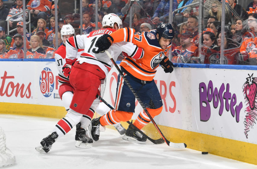 EDMONTON, AB - JANUARY 20: Milan Lucic #27 of the Edmonton Oilers battles for the puck against Dougie Hamilton #19 of the Carolina Hurricanes on January 20, 2019 at Rogers Place in Edmonton, Alberta, Canada. (Photo by Andy Devlin/NHLI via Getty Images)