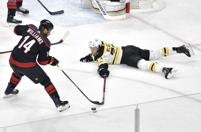 RALEIGH, NORTH CAROLINA - MAY 14: Charlie McAvoy #73 of the Boston Bruins looks for the puck as he slides on the ice against Justin Williams #14 of the Carolina Hurricanes during the first period in Game Three of the Eastern Conference Finals during the 2019 NHL Stanley Cup Playoffs at PNC Arena on May 14, 2019 in Raleigh, North Carolina. (Photo by Grant Halverson/Getty Images)