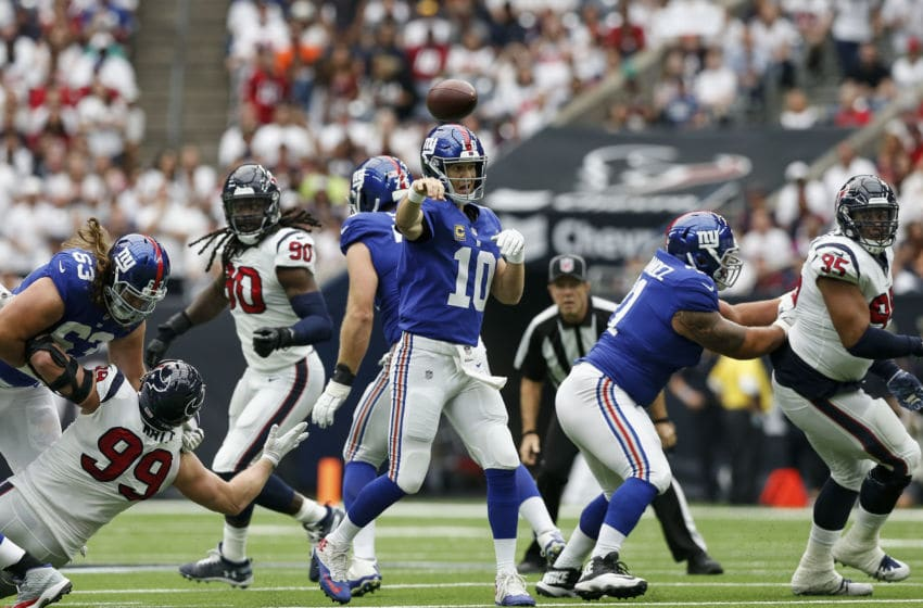 HOUSTON, TX - SEPTEMBER 23: Eli Manning #10 of the New York Giants throws a pass pressured by J.J. Watt #99, Jadeveon Clowney #90 and Christian Covington #95 of the Houston Texans in the second quarter at NRG Stadium on September 23, 2018 in Houston, Texas. (Photo by Tim Warner/Getty Images)