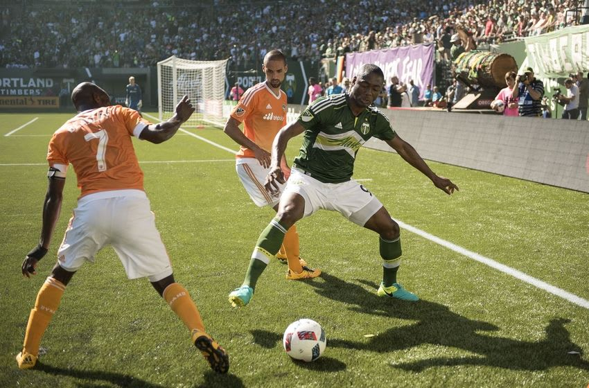 June 26, 2016; Portland, OR, USA; Portland Timbers forward Fanendo Adi (9) is defended by Houston Dynamo defender DaMarcus Beasley (7) and defender Raul Rodriquez (5) during the second half at Providence Park. The Timbers won 3-2. Mandatory Credit: Troy Wayrynen-USA TODAY Sports