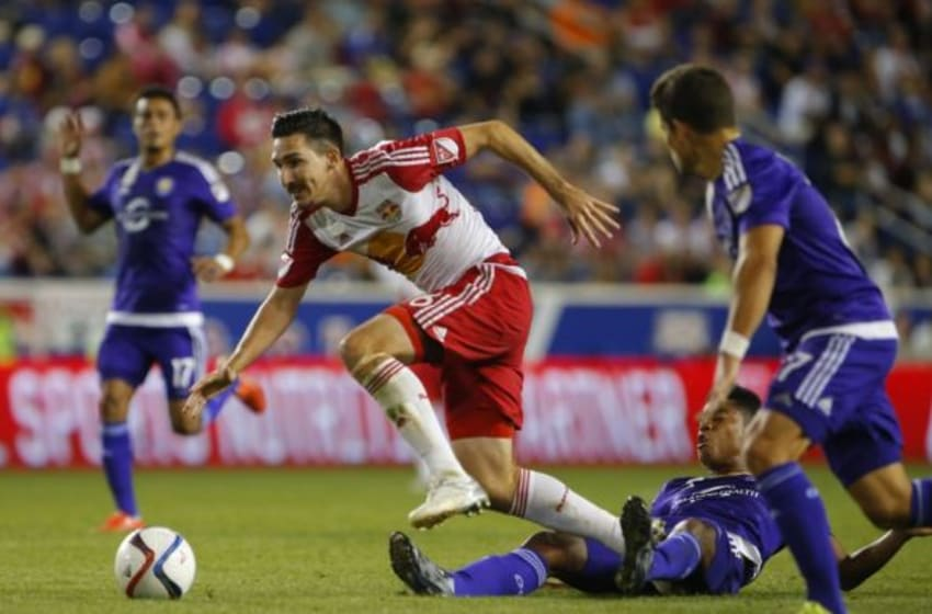 Sep 25, 2015; Harrison, NJ, USA; New York Red Bulls midfielder Sacha Kljestan (16) goes down after a slide tackle by Orlando City FC midfielder Cristian Higuita (7) during first half at Red Bull Arena. Mandatory Credit: Noah K. Murray-USA TODAY Sports