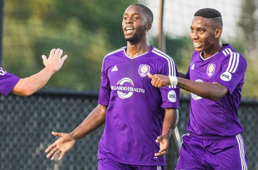 Lewis Neal and Bryan Rochez celebrate OCB's early goal with goal scorer, Michael Cox (middle)