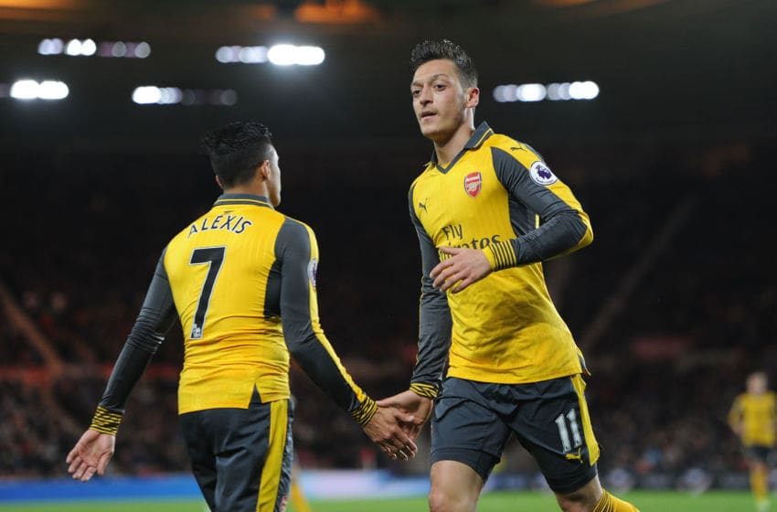 MIDDLESBROUGH, ENGLAND - APRIL 17: Mesut Ozil high fives Alexis Sanchez of Arsenal during the Premier League match between Middlesbrough and Arsenal at Riverside Stadium on April 17, 2017 in Middlesbrough, England. (Photo by David Price/Arsenal FC via Getty Images)