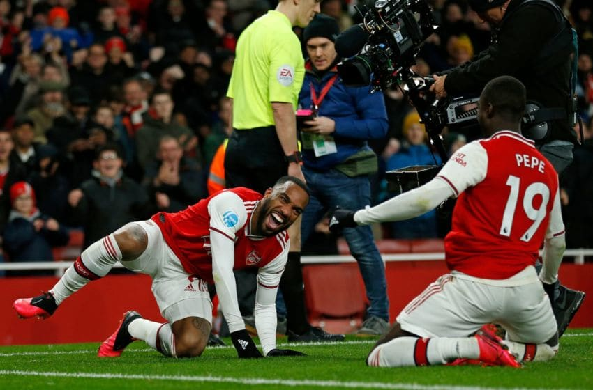 Arsenal's French striker Alexandre Lacazette celebrates with Arsenal's French-born Ivorian midfielder Nicolas Pepe (R) after scoring their fourth goal during the English Premier League football match between Arsenal and Newcastle United at the Emirates Stadium in London on February 16, 2020. - Arsenal won the game 4-0. (Photo by Ian KINGTON / AFP) / RESTRICTED TO EDITORIAL USE. No use with unauthorized audio, video, data, fixture lists, club/league logos or 'live' services. Online in-match use limited to 120 images. An additional 40 images may be used in extra time. No video emulation. Social media in-match use limited to 120 images. An additional 40 images may be used in extra time. No use in betting publications, games or single club/league/player publications. / (Photo by IAN KINGTON/AFP via Getty Images)