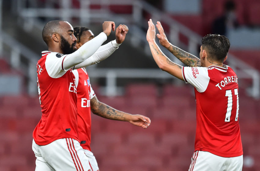 Arsenal's French striker Alexandre Lacazette (L) celebrates scoring a goal with Arsenal's Uruguayan midfielder Lucas Torreira (R) during the English Premier League football match between Arsenal and Liverpool at the Emirates Stadium in London on July 15, 2020. (Photo by Glyn KIRK / POOL / AFP) / RESTRICTED TO EDITORIAL USE. No use with unauthorized audio, video, data, fixture lists, club/league logos or 'live' services. Online in-match use limited to 120 images. An additional 40 images may be used in extra time. No video emulation. Social media in-match use limited to 120 images. An additional 40 images may be used in extra time. No use in betting publications, games or single club/league/player publications. / (Photo by GLYN KIRK/POOL/AFP via Getty Images)