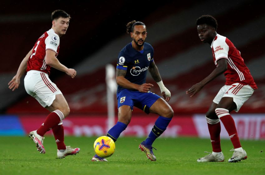 Southampton's English midfielder Theo Walcott (C) vies with Arsenal's Scottish defender Kieran Tierney (L) and Arsenal's English striker Bukayo Saka during the English Premier League football match between Arsenal and Southampton at the Emirates Stadium in London on December 16, 2020. (Photo by Adrian DENNIS / POOL / AFP) / RESTRICTED TO EDITORIAL USE. No use with unauthorized audio, video, data, fixture lists, club/league logos or 'live' services. Online in-match use limited to 120 images. An additional 40 images may be used in extra time. No video emulation. Social media in-match use limited to 120 images. An additional 40 images may be used in extra time. No use in betting publications, games or single club/league/player publications. / (Photo by ADRIAN DENNIS/POOL/AFP via Getty Images)