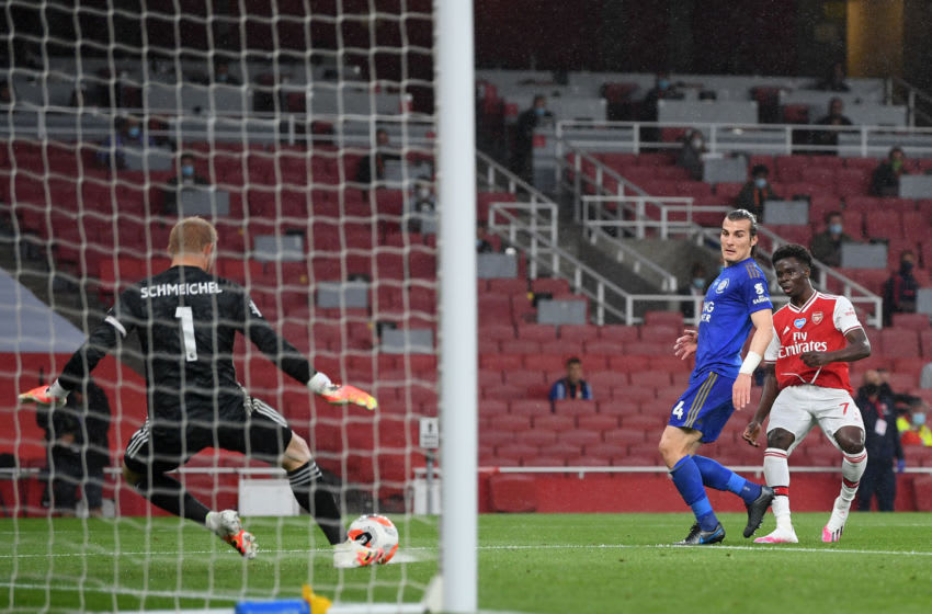 LONDON, ENGLAND - JULY 07: Kasper Schmeichel of Leicester City makes a save from Bukayo Saka of Arsenal during the Premier League match between Arsenal FC and Leicester City at Emirates Stadium on July 07, 2020 in London, England. Football Stadiums around Europe remain empty due to the Coronavirus Pandemic as Government social distancing laws prohibit fans inside venues resulting in all fixtures being played behind closed doors. (Photo by Michael Regan/Getty Images)