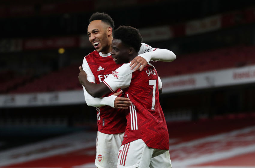 LONDON, ENGLAND - JANUARY 18: Bukayo Saka of Arsenal (R) celebrates with teammate Pierre-Emerick Aubameyang after scoring their team's second goal during the Premier League match between Arsenal and Newcastle United at Emirates Stadium on January 18, 2021 in London, England. Sporting stadiums around England remain under strict restrictions due to the Coronavirus Pandemic as Government social distancing laws prohibit fans inside venues resulting in games being played behind closed doors. (Photo by Catherine Ivill/Getty Images)
