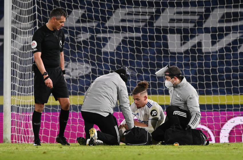 LEEDS, ENGLAND - FEBRUARY 08: Kalvin Phillips of Leeds United receives treatment from staff in PPE during the Premier League match between Leeds United and Crystal Palace at Elland Road on February 08, 2021 in Leeds, England. Sporting stadiums around the UK remain under strict restrictions due to the Coronavirus Pandemic as Government social distancing laws prohibit fans inside venues resulting in games being played behind closed doors. (Photo by Stu Forster/Getty Images)