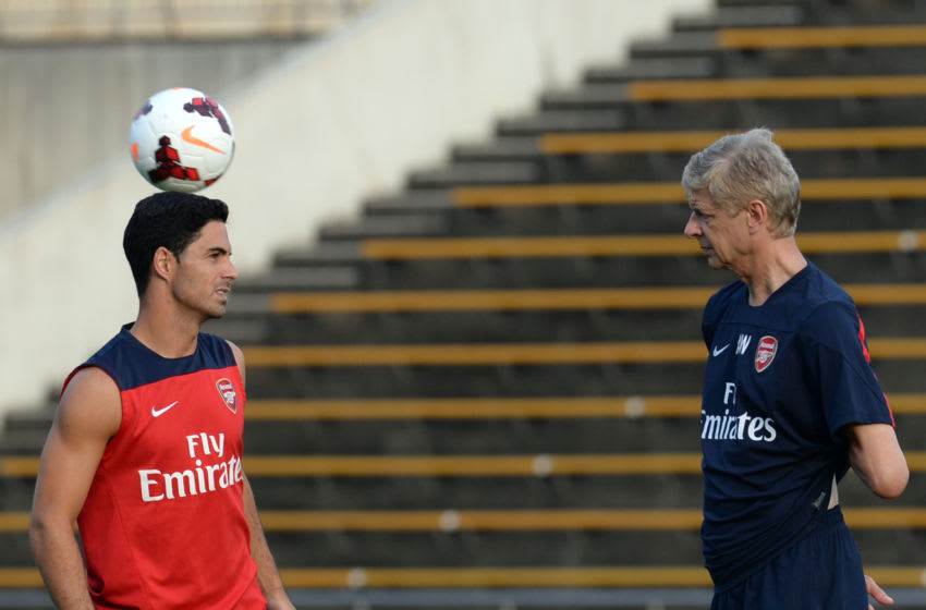 Arsenal midfielder Mikel Arteta (L) chats with head coach Arsene Wenger (R) during their training session in Nagoya on July 21, 2013. Arsenal's Japanese leg of their pre-season Asian tour is a trip down memory lane for Arsene Wenger, as he faces former club Nagoya Grampus -- coached by one of his ex-players. AFP PHOTO / TOSHIFUMI KITAMURA (Photo credit should read TOSHIFUMI KITAMURA/AFP via Getty Images)
