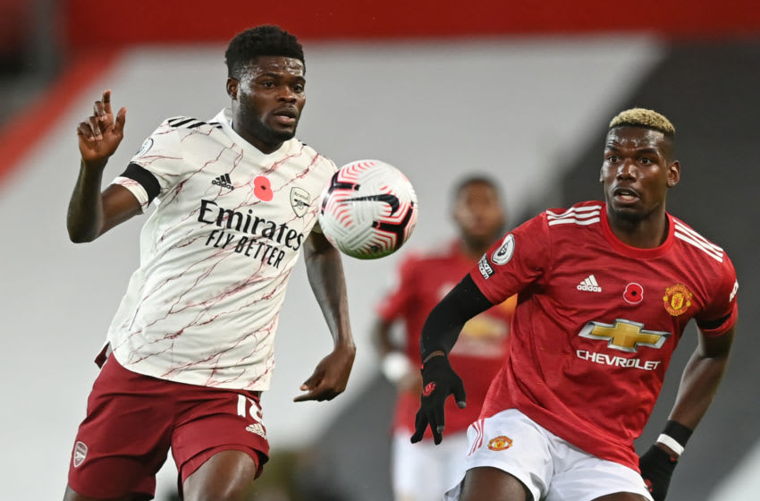 Arsenal's Ghanaian midfielder Thomas Partey (L) vies with Manchester United's French midfielder Paul Pogba (R) during the English Premier League football match between Manchester United and Arsenal at Old Trafford in Manchester, north west England, on November 1, 2020. (Photo by Shaun Botterill / POOL / AFP) / RESTRICTED TO EDITORIAL USE. No use with unauthorized audio, video, data, fixture lists, club/league logos or 'live' services. Online in-match use limited to 120 images. An additional 40 images may be used in extra time. No video emulation. Social media in-match use limited to 120 images. An additional 40 images may be used in extra time. No use in betting publications, games or single club/league/player publications. / (Photo by SHAUN BOTTERILL/POOL/AFP via Getty Images)