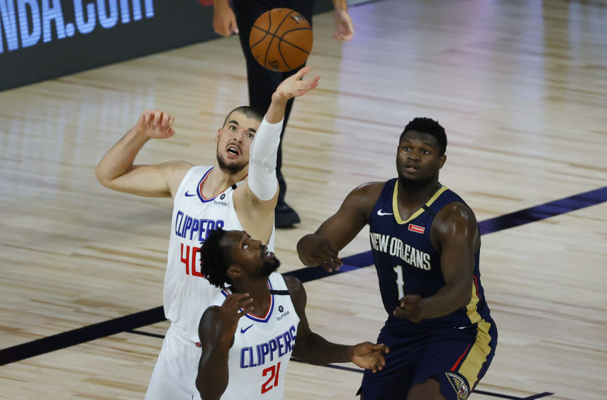 Ivica Zubac #40 and Patrick Beverley #21 of the LA Clippers chase a loose ball against Zion Williamson #1 of the New Orleans Pelicans (Photo by Kevin C. Cox/Getty Images)