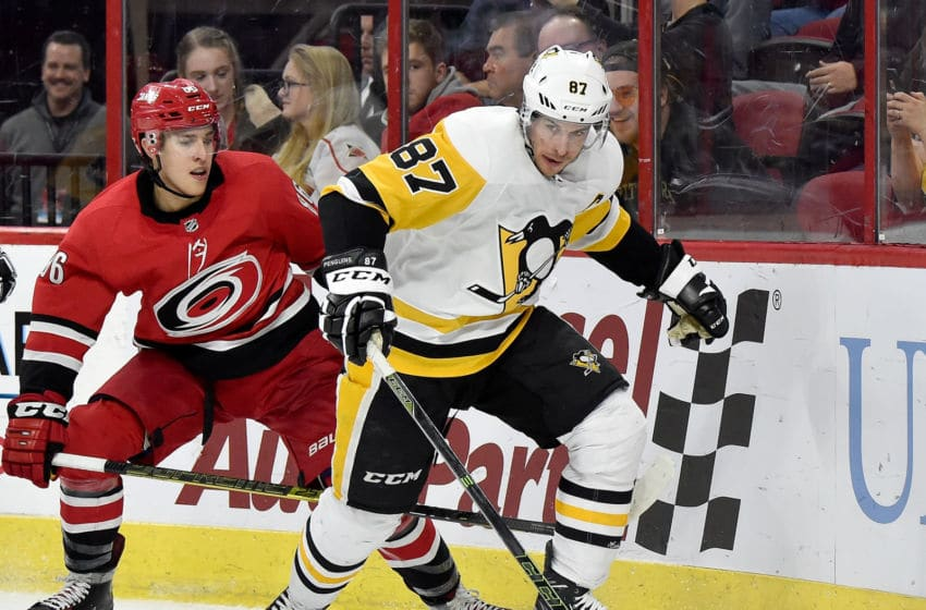 RALEIGH, NORTH CAROLINA - DECEMBER 22: Sidney Crosby #87 of the Pittsburgh Penguins moves the puck against Teuvo Teravainen #86 of the Carolina Hurricanes during the third period of their game at PNC Arena on December 22, 2018 in Raleigh, North Carolina. The Penguins won 3-0. (Photo by Grant Halverson/Getty Images)