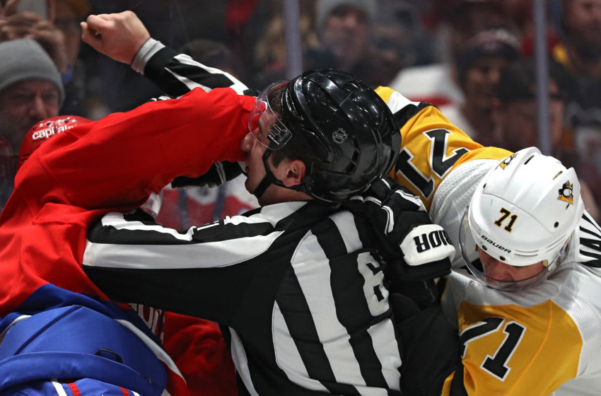 WASHINGTON, DC - FEBRUARY 23: Linesman James Tobias breaks up Evgeni Malkin #71 of the Pittsburgh Penguins and Brenden Dillon #4 of the Washington Capitals during the first period at Capital One Arena on February 23, 2020 in Washington, DC. (Photo by Patrick Smith/Getty Images)
