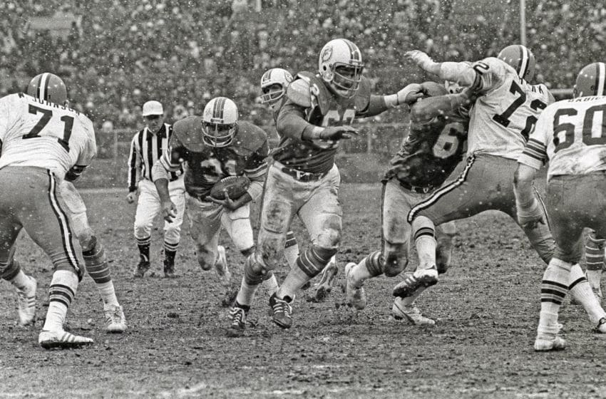 CLEVELAND, OH - NOVEMBER 28: (EDITORS NOTE: Image has been shot in black and white. Color version not available.) Running back Norm Bulaich #31 of the Miami Dolphins runs behind the blocking of center Jim Langer #62 and guard Bob Kuechenberg #67 as defensive linemen Walter Johnson #71 and Jerry Sherk #72 and linebacker Bob Babich #60 of the Cleveland Browns pursue the play as snow falls during a game at Cleveland Municipal Stadium on November 28, 1976 in Cleveland, Ohio. The Browns defeated the Dolphins 17-13. (Photo by George Gojkovich/Getty Images)
