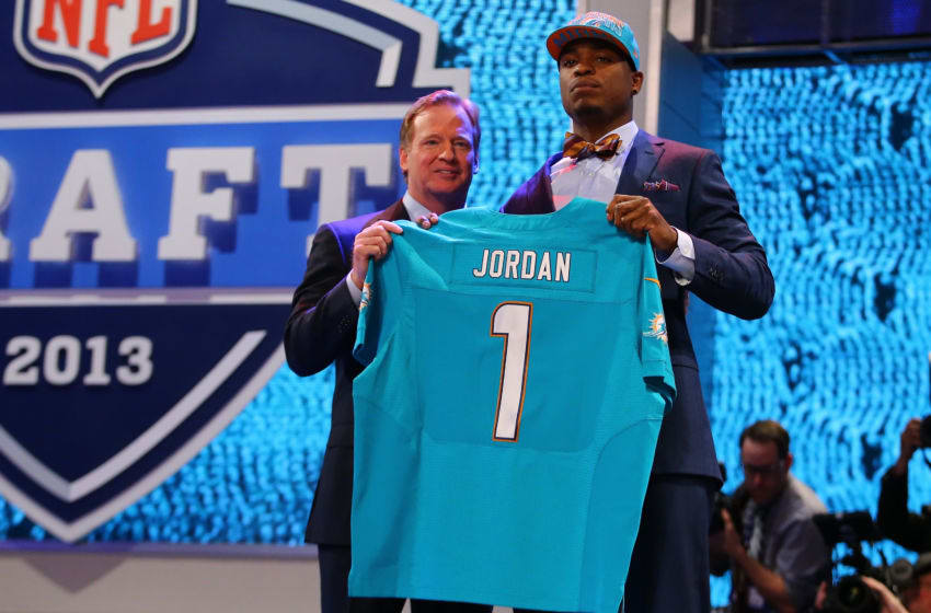 NEW YORK, NY - APRIL 25: Dion Jordan (R) of the Oregon Ducks stands with NFL Commissioner Roger Goodell as they hold up a jersey on stage after he was picked #3 overall by the Miami Dolphins in the first round of the 2013 NFL Draft at Radio City Music Hall on April 25, 2013 in New York City. (Photo by Al Bello/Getty Images)