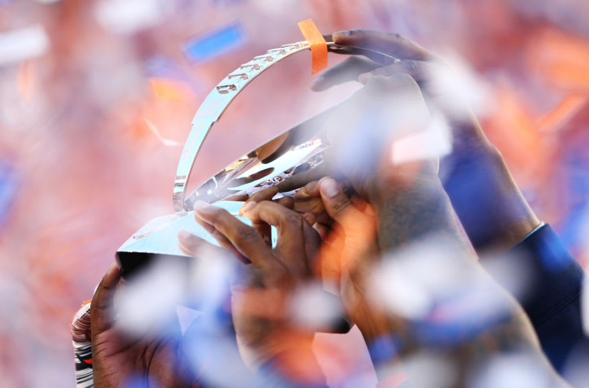 DENVER, CO - JANUARY 19: The Denver Broncos hold up the Lamar Hunt Trophy after defeating the New England Patriots 26 to 16 in the AFC Championship game at Sports Authority Field at Mile High on January 19, 2014 in Denver, Colorado. (Photo by Elsa/Getty Images)