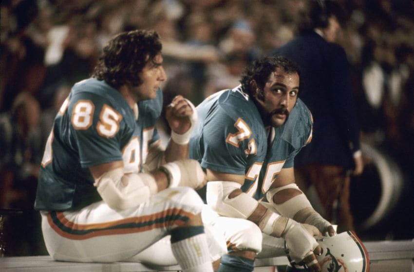 MIAMI, FL - NOVEMBER 27, 1972: (L to R) Linebacker Nick Buoniconti #85 and defensive lineman Manny Fernandez #75, of the Miami Dolphins, on the bench during a game against the St. Louis Cardinals on November 27, 1972 at the Orange Bowl in Miami, Florida. (Photo by: Kidwiler Collection/Diamond Images/Getty Images)
