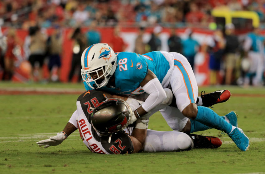 TAMPA, FLORIDA - AUGUST 16: Bobby McCain #28 of the Miami Dolphins tackles Antony Auclair #82 of the Tampa Bay Buccaneers in the second half during the preseason game at Raymond James Stadium on August 16, 2019 in Tampa, Florida. (Photo by Mike Ehrmann/Getty Images)