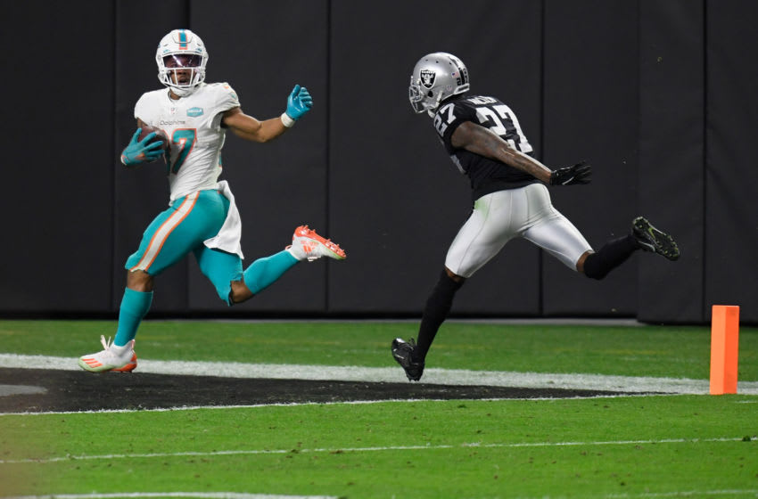 LAS VEGAS, NEVADA - DECEMBER 26: Myles Gaskin #37 of the Miami Dolphins scores a touchdown in front of Trayvon Mullen #27 of the Las Vegas Raiders to take the lead in the fourth quarter of a game at Allegiant Stadium on December 26, 2020 in Las Vegas, Nevada. (Photo by Harry How/Getty Images)