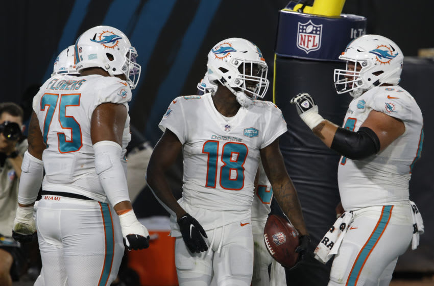 Sep 24, 2020; Jacksonville, Florida, USA; Miami Dolphins wide receiver Preston Williams (18) celebrates with center Ted Karras (right) and offensive guard Ereck Flowers (75) after making a touchdown catch against the Jacksonville Jaguars during the first quarter at TIAA Bank Field. Mandatory Credit: Reinhold Matay-USA TODAY Sports