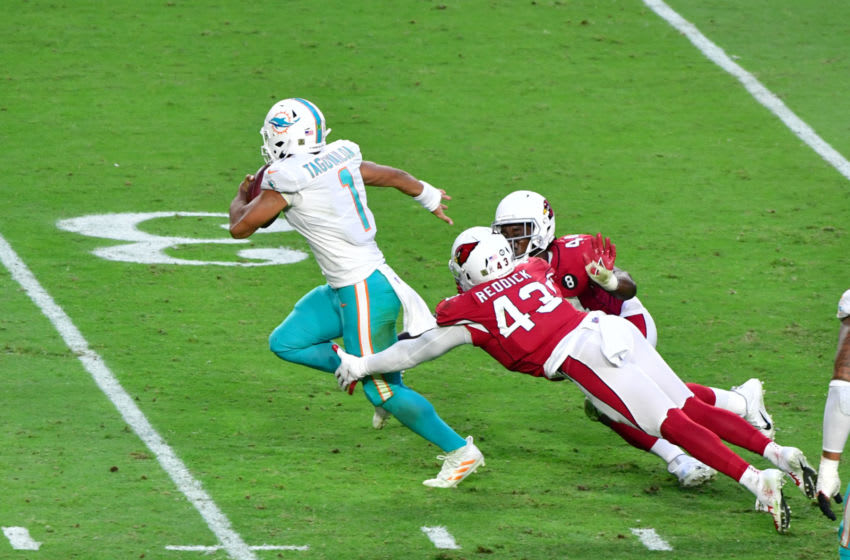 Nov 8, 2020; Glendale, Arizona, USA; Miami Dolphins quarterback Tua Tagovailoa (1) slips a tackle by Arizona Cardinals outside linebacker Haason Reddick (43) and linebacker Isaiah Simmons (48) during the second half at State Farm Stadium. Mandatory Credit: Matt Kartozian-USA TODAY Sports
