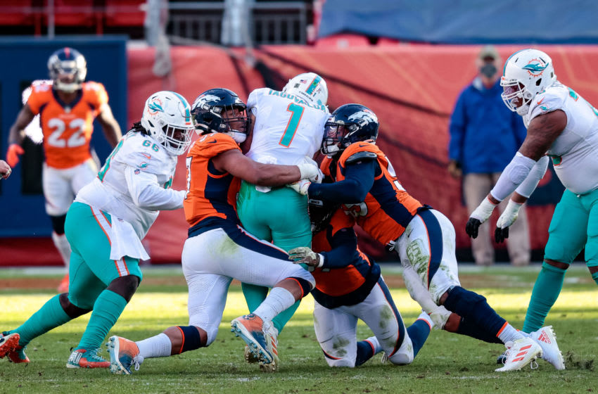 Nov 22, 2020; Denver, Colorado, USA; Miami Dolphins quarterback Tua Tagovailoa (1) is sacked by Denver Broncos defensive end DeMarcus Walker (57) and outside linebacker Bradley Chubb (55) and outside linebacker Malik Reed (59) in the second quarter at Empower Field at Mile High. Mandatory Credit: Isaiah J. Downing-USA TODAY Sports