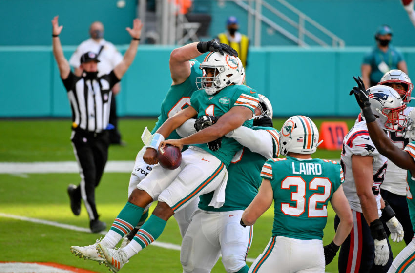 Dec 20, 2020; Miami Gardens, Florida, USA; Miami Dolphins quarterback Tua Tagovailoa (1) celebrates with teammates after scoring a touchdown against the New England Patriots during the second half at Hard Rock Stadium. Mandatory Credit: Jasen Vinlove-USA TODAY Sports