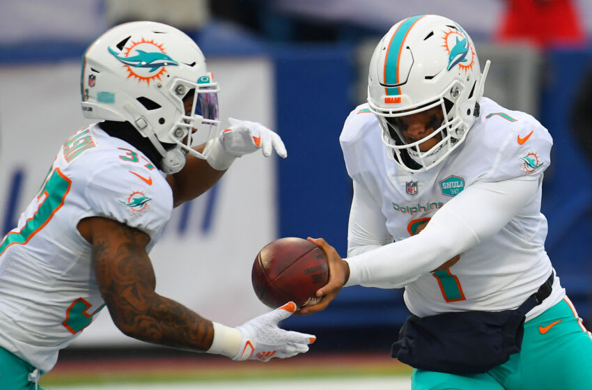 Jan 3, 2021; Orchard Park, New York, USA; Miami Dolphins quarterback Tua Tagovailoa (1) hands the ball off to running back Myles Gaskin (37) against the Buffalo Bills during the first quarter at Bills Stadium. Mandatory Credit: Rich Barnes-USA TODAY Sports