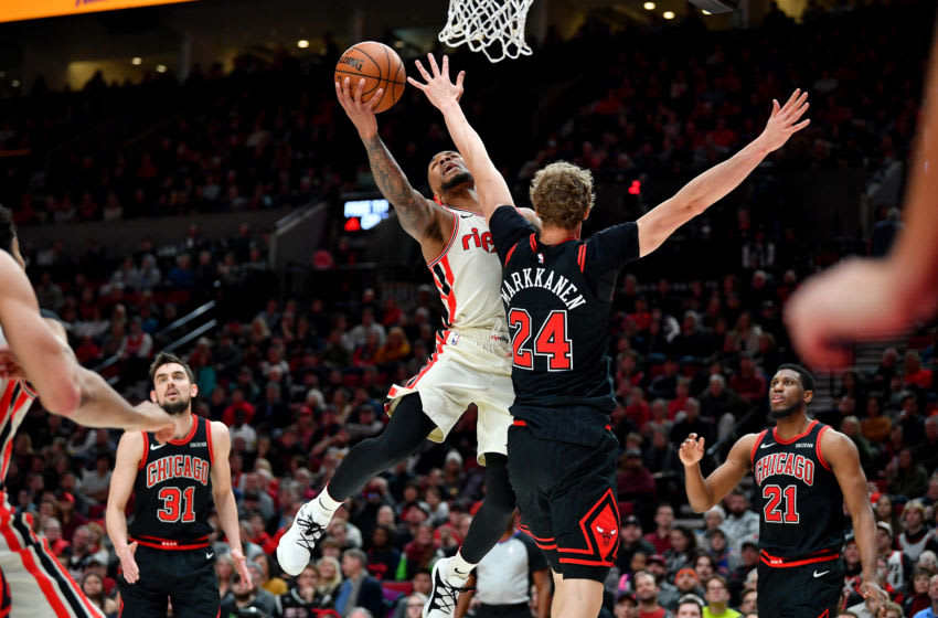 PORTLAND, OREGON - NOVEMBER 29: Damian Lillard #0 of the Portland Trail Blazers is fouled by Lauri Markkanen #24 of the Chicago Bulls while driving to the basket during the first half of the game at the Moda Center on November 29, 2019 in Portland, Oregon. The Trail Blazers won 107-103. NOTE TO USER: User expressly acknowledges and agrees that, by downloading and or using this photograph, User is consenting to the terms and conditions of the Getty Images License Agreement. (Photo by Alika Jenner/Getty Images)
