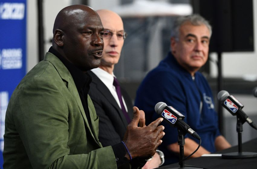 Former NBA star and owner of Charlotte Hornets team Michael Jordan (L) is watched by NBA commissioner Adam Silver (C) and Marc Lasry co-owner of the Milwaukee Bucks (R) as he addresses a press conference ahead of the NBA basketball match between Milwaukee Bucks and Charlotte Hornets at The AccorHotels Arena in Paris on January 24, 2020. (Photo by Anne-Christine POUJOULAT / AFP) (Photo by ANNE-CHRISTINE POUJOULAT/AFP via Getty Images)
