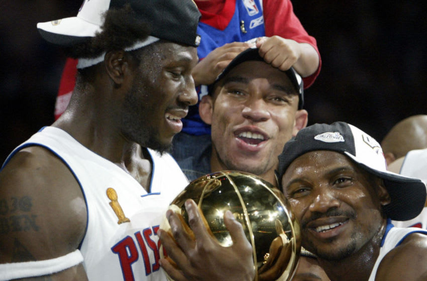 AUBURN HILLS, UNITED STATES: Ben Wallace (L) Darvin Ham (C) and Lindsey Hunter (R) of the Detroit Pistons holds the Larry O'Brien trophy after beating the Los Angeles Lakers in game five of the NBA Finals to win the NBA championship 15 June, 2004 at The Palace in Auburn Hills, MI. The Pistons won the game 100-87 to win the best-of-seven game series 4-1. AFP PHOTO/Jeff HAYNES (Photo credit should read JEFF HAYNES/AFP via Getty Images)