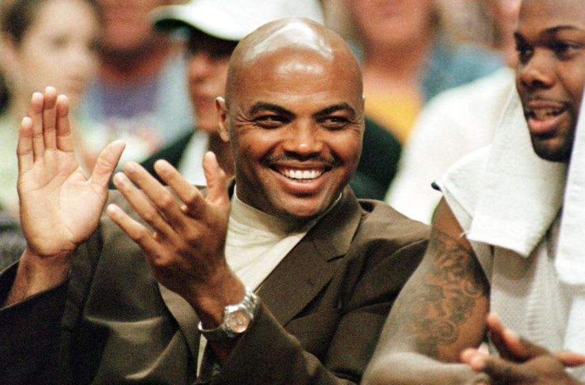 PHOENIX, AZ - APRIL 18: Injured Houston Rockets forward Charles Barkley (L) claps after his team scored against the Phoenix Suns during the second quarter, 18 April 2000 in Phoenix. Barkley, who was rumored to be dressed for tonight's game, will play in the Rockets' last regular season game against the Vancouver Grizzlies on 19 April 2000. The Rockets won 107-98. (Photo credit should read MIKE FIALA/AFP via Getty Images)