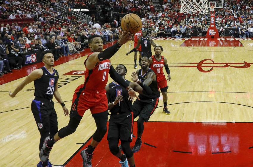 HOUSTON, TEXAS - MARCH 05: Russell Westbrook #0 of the Houston Rockets drives to the basket while defended by Reggie Jackson #1 of the LA Clippers and Landry Shamet #20 in the second half at Toyota Center on March 05, 2020 in Houston, Texas. NOTE TO USER: User expressly acknowledges and agrees that, by downloading and or using this photograph, User is consenting to the terms and conditions of the Getty Images License Agreement. (Photo by Tim Warner/Getty Images)