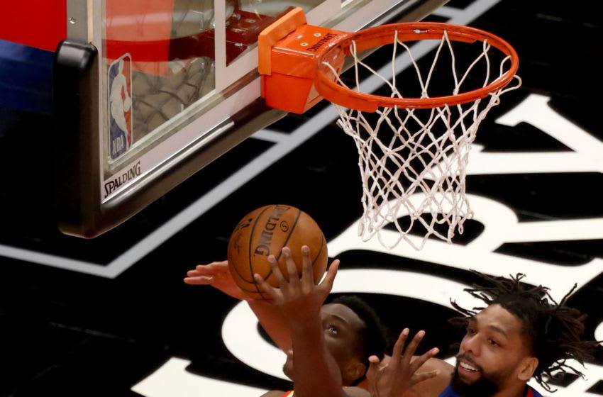 Jan 20, 2021; Atlanta, Georgia, USA; Atlanta Hawks center Onyeka Okongwu (17) attempts a basket against Detroit Pistons point guard Delon Wright (55) and center Jahlil Okafor (13) during the second quarter at State Farm Arena. Mandatory Credit: Jason Getz-USA TODAY Sports